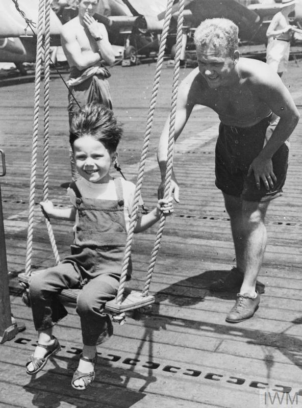 TOYS FROM THE ROYAL NAVY FOR CHILDREN FROM JAPANESE CAMPS. SEPTEMBER 1945. REPATRIATED PRISONERS OF WAR AND CIVILIAN INTERNEES BROUGHT TO SYDNEY, AUSTRALIA, IN THE BRITISH PACIFIC FLEET ESCORT CARRIER HMS RULER, INCLUDED SEVERAL CHILDREN. MEMBERS OF THE RULER'S CREW MADE TOYS FOR THESE CHILDREN DURING THE VOYAGE.
