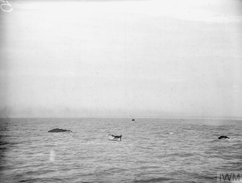 LIFEBOAT DROPPED FROM AIR. 13 JULY 1945, LEE-ON-SOLENT. THE DEMONSTRATION DROP OF THE NAVY'S AIRBORNE LIFEBOAT, 17 FT, 9 INS LONG, WHEN IT WAS DROPPED BY PARACHUTE TO AN AIR CREW WHO WERE SUPPOSED TO HAVE FORCED LANDED INTO THE SEA. THE LIFEBOAT, SELF-RIGHTING, AND SELF-BALING IS EQUIPPED WITH SAILS AND AN OUTBOARD ENGINE WHICH GIVES IT A RANGE OF 120 MILES AT 4 KNOTS.