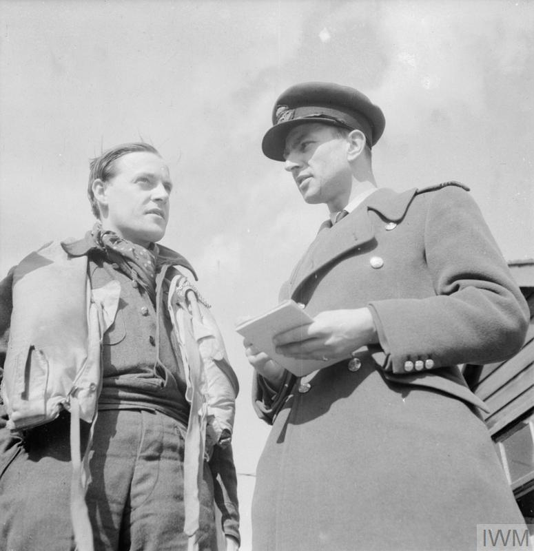 Squadron Leader P M Brothers (left) Commanding Officer of No. 457 Squadron RAAF, describing a sweep over northern France to the Squadron Intelligence Officer at Redhill, Surrey. Brothers was a Battle of Britain veteran who flew with Nos. 32 and 257 Squadrons RAF during the Battle of Britain.