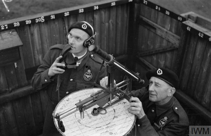 "Using a chest telephone, Mr P C ""Lofty"" Austin, former commercial traveller and ex-professional footballer for Tottenham Hotspur, reports to the Corps Centre, as Mr E C ""Smudge"" Smith works the plotting instrument in an ROC post at Kings Langley, Hertfordshire."