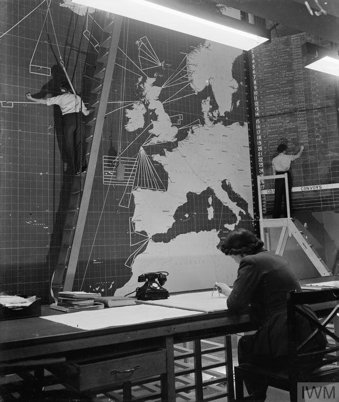 The interior of the Operations Room at Coastal Command Headquarters at Eastbury Park, Northwood, Middlesex. A WAAF officer in the foreground is plotting the course of an aircraft, while two WAAF special duties clerks alter the position of a convoy. The clerk on the ladder is wearing a safety harness.