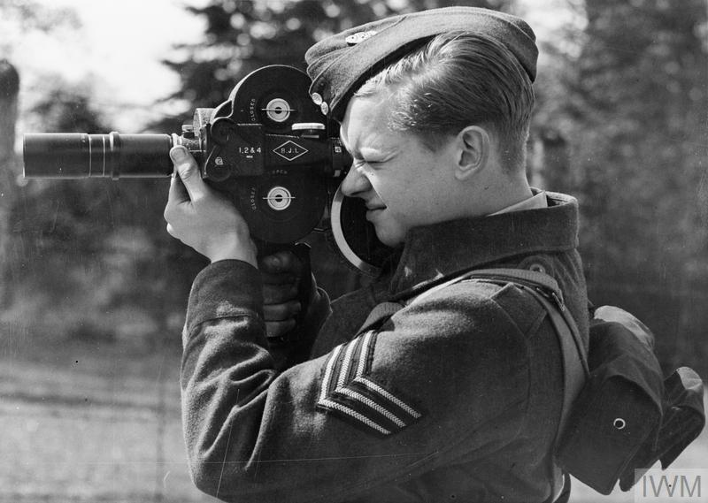A cameraman of the RAFFPU poses, focussing a Bell & Howell Eyemo 35mm film camera with a telephoto lens.