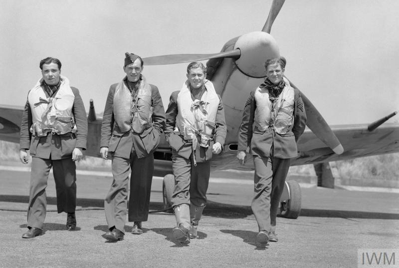 Four pilots of No. 611 Squadron RAF walking away from a Supermarine Spitfire Mark VB at Hornchurch, Essex, after a daylight sweep over France. They are (left to right): Flight-Lieutenant E S Lock, Pilot Officer W G G Duncan-Smith, Flying Officer P G Dexter, and Sergeant W M Gilmour. Lock arrived at 611 Squadron as a flight commander, having already shot down 24 enemy aircraft.