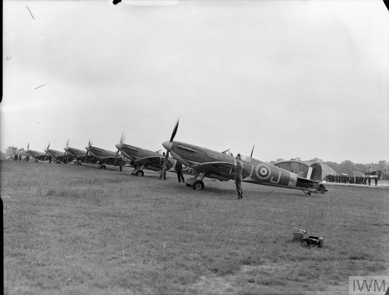 A flight of Supermarine Spitfire Mk VBs of No. 92 Squadron RAF in line with engines running at Biggin Hill, Kent. The nearest aircraft, R7161 'QJ-J', is a converted Mark I.