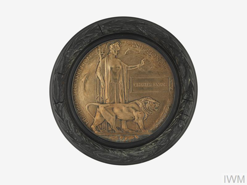 Highly polished Next of Kin Memorial Plaque in a circular dark wood veneered frame decorated with carved (or moulded) laurel leaves. The name on the plaque is Charles Evans.