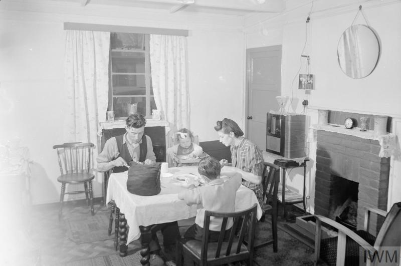 A family sit down for a meal in their prefabricated emergency house.
