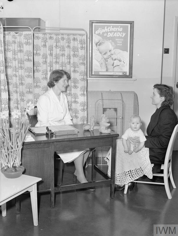 A mother and baby having a consultation with a health visitor in her office.