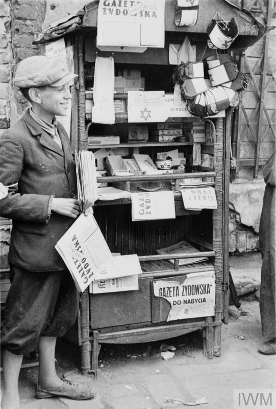 "An young and cheerful seller of newspapers and armbands running his stall in the street of the ghetto (possibly Muranowski Square). The title of the newspaper for sale is ""Gazeta Żydowska - Jewish Gazette"". He also advertises Wrigley's chewing gum for sale, mispelled as Wirgley's."