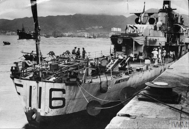 Black Swan-class sloop HMS Amethyst (F116) docked at Hong Kong, showing a shell hole in its stern. The discs on the mooring ropes prevent rats from boarding the ship. The Amethyst had travelled to Hong Kong under darkness from the Communist-held Yangtze River area. 10th August 1949.