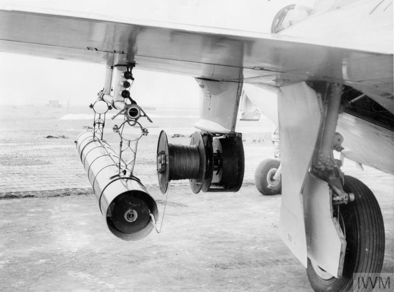NEW BANNER (TARGET) STREAMING DEVICE. 1954? ROYAL NAVAL AIR STATION LOSSIEMOUTH, SCOTLAND. THE EXCELSIOR TARGET STREAMING DEVICE DEVELOPED FOR THE NAVY. EXCELSIOR ALLOWS A BANNER TO BE TOWED IN A SQUADRON AIRCRAFT TAKING OFF AT THE SAME TIME AND FROM THE SAME AIRFIELD AS FIRING AIRCRAFT, THE BANNER BEING PAID OUT WHILE IN THE AIR. THE EXCELSIOR HAS AT ITS HEART A FLUID FLY WHEEL, A DRUM CARRIES THE TOWING WIRE AND A SLIP MECHANISM OPERATED BY A BOMB RELEASE UNIT ENABLES THE BANNER TO BE RELEASED AT ANY TIME. EXCELSIOR IS TO BE USED ON SEA HAWK FGA MK 4 AIRCRAFT. IT WILL MAKE IT POSSIBLE TO CARRY OUT TARGET PRACTICE AT HIGHER SPEEDS AND ENABLE SQUADRONS EMBARKED IN AIRCRAFT CARRIERS TO HAVE TARGET PRACTICE AS WELL. THE INITIAL DEVELOPMENT OF THE EXCELSIOR WAS CARRIED OUT AT ROYAL NAVAL AIR STATION LOSSIEMOUTH IN 802 SQUADRON, SEA HAWK F1 AIRCRAFT AS SHOWN IN THIS SERIES.
