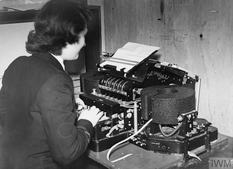 A woman sits and uses a Typex Mark II cryptograph machine