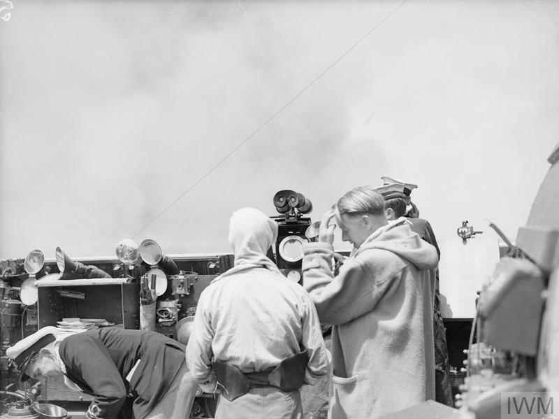 THE NAVY'S PART IN THE ITALY ADVANCE. 12 MAY 1944, ON BOARD THE CRUISER HMS DIDO, IN THE MEDITERRANEAN. THE DIDO WITH AN ESCORT OF AMERICAN DESTROYERS CARRIED OUT HARASSING FIRE ON THE APPIAN WAY IN THE TERRACINA AREA, AND UPON ENEMY HEAVY ARTILLERY OPPOSING THE FIFTH ARMY IN THE GAETA AREA. CAP Officers and men against a background of billowing smoke from the guns of the cruiser during the bombardment.