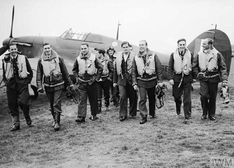 A group of pilots of No. 303 Polish Fighter Squadron walking towards the camera from a Hawker Hurricane (probably Hurricane Mk.I, RF-F, V6684) after returning from a fighter sortie at RAF Leconfield, 24 October 1940.