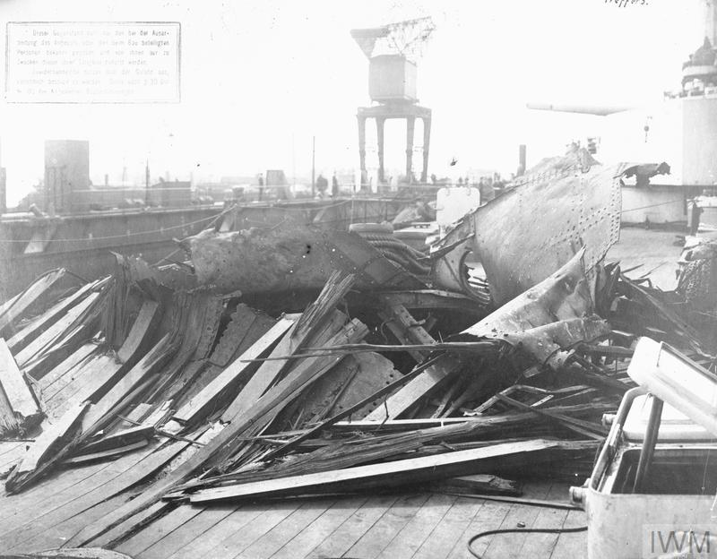 Damage to the deck the German battlecruiser DERFFLINGER sustained at the battle of Jutland and photographed after she had returned to port, part of which can be seen in the background. She had been hit by ten 15 inch shells, one 13.5 inch shell and ten twelve inch shells. Both after turrets were put out of action with serious cartridge fires by 15 inch shells from REVENGE, while other 15 inch hits had earlier caused flooding forward.