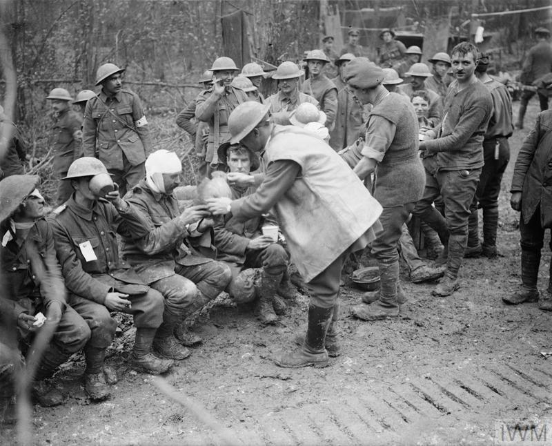 Battle of the Ancre 13 - 18 November 1916: Wounded British troops at a Dressing Station in Aveluy Wood. One man shows damage to his steel helmet from which he suffered a head wound. 13 November 1916.
