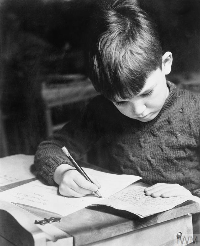 A portrait of a young British evacuee as he writes at a desk at his new school  © IWM CAN 224