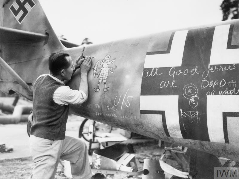 A member of staff at a technical college removes the 'Mickey Mouse' staffel emblem a shot-down German Messerschmitt Bf 109.