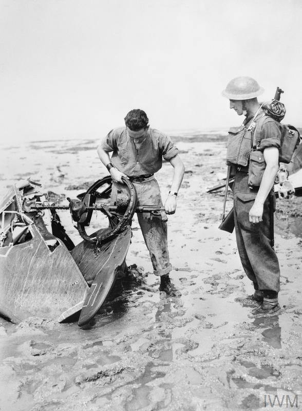 Soldiers examine an MG 17 machine gun and part of the tail of a Dornier Do 17Z of KG 2, shot down 13 August 1940.