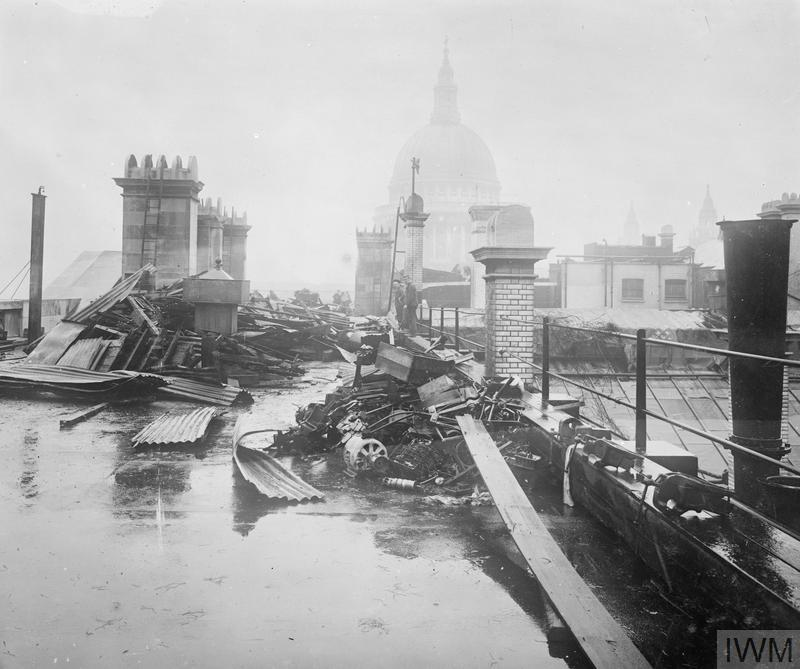 A view of the roof of the General Post Office, looking across to St Paul's Cathedral in the background, showing piles of salvaged materials and debris piled on the roof following a raid which occurred on 7 July 1917. This was the second daylight aeroplane raid on London and the damage was caused by a 15 kilogram bomb.