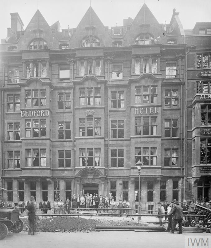 A group of people stand outside the Bedford Hotel on Southampton Row to watch at men at work beside a large crater. The damage was caused by a 50 kilogram bomb during a Gotha raid on the night of 24 - 25 September 1917.