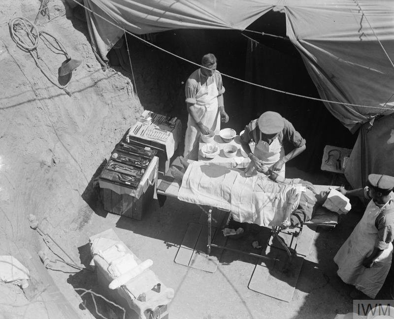 Surgery in progress at a Casualty Clearing Station in Gallipoli. The surgeon is removing a bullet from the patient's right arm.