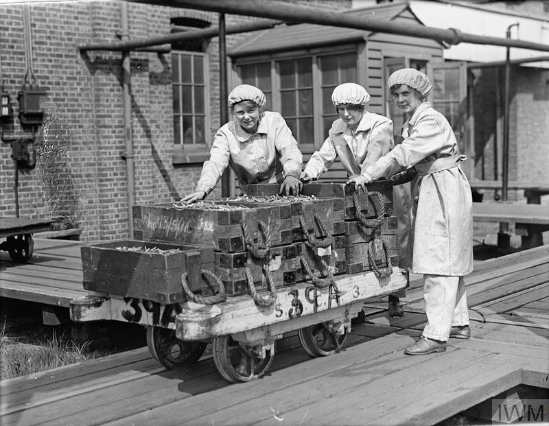 Three female munitions workers push a wagon laden with cartridge cases at Woolwich Arsenal, May 1918.