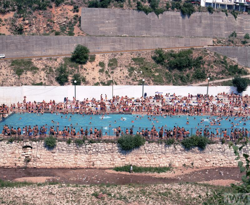 From the series 'AfterWars'. 1 from edition of 5. Framed. image: A swimming pool, crowded with bathers and spectators. In the foreground below the pool's retaining wall is an area of waste land, and behind the pool is a main road with high concrete retaining walls, zig-zagging up a steep hill.