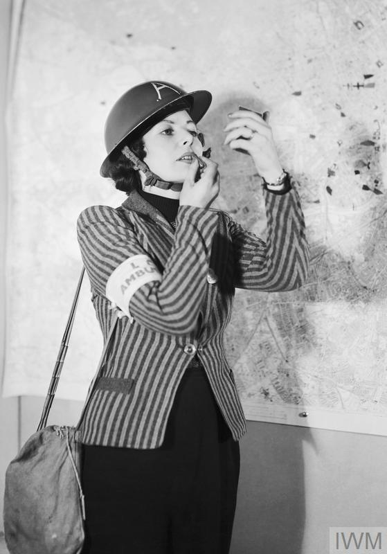 An Air Raid Precautions (ARP) volunteer applies her lipstick between emergency calls, c.1940.