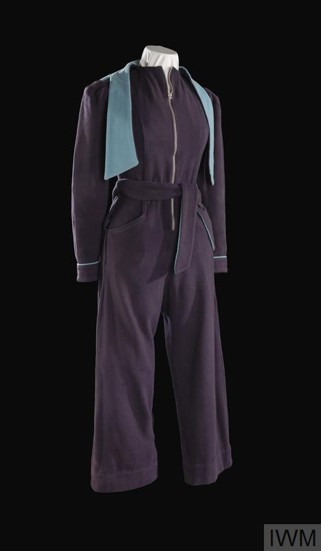 Zip fronted step-in overalls style garment of dark blue fabric, having bell-bottom cuffs to the legs, and with a fitted hood. The hood is lined in Cambridge blue fabric, as is the detachable waist belt and piping decoration to the cuffs. The shoulders are decoratively puffed.