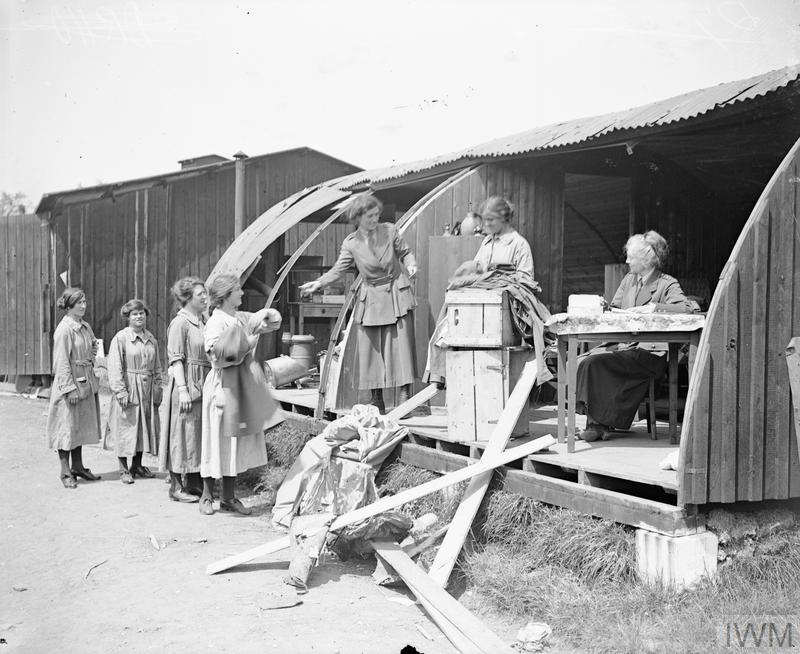 Clothing is being issued by the Women's Army Auxiliary Corps (WAAC) from a Nissen hut damaged by an air raid at Abbeville, 22 May 1918.