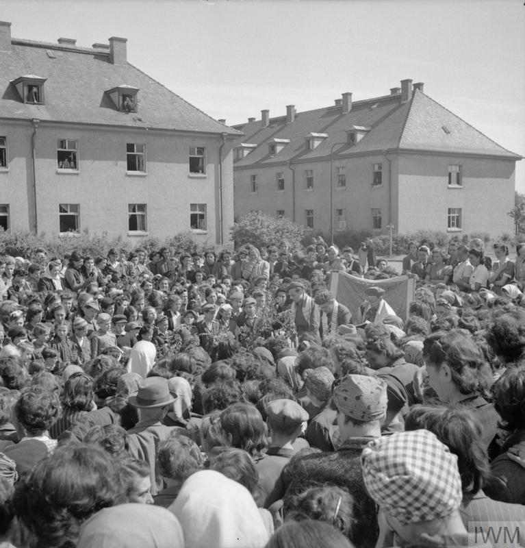 Jewish camp inmates hold an open air service to celebrate the Jewish Summer Festival of Thanksgiving. The service was led by Rev Leslie H Hardman, Senior Jewish Chaplain to the British 2nd Army, and former camp inmates, Rabbi H Helfgott of Jugoslovia and Rabbi B Goldfinger of Poland.
