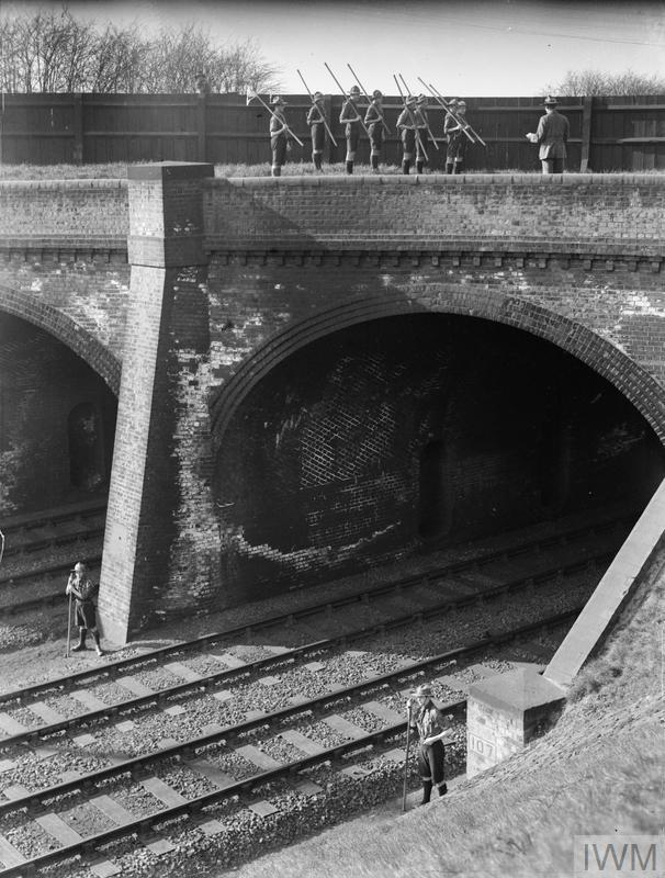 Boy scouts on guard by a railway bridge and train tracks in the United Kingdom during the First World War.
