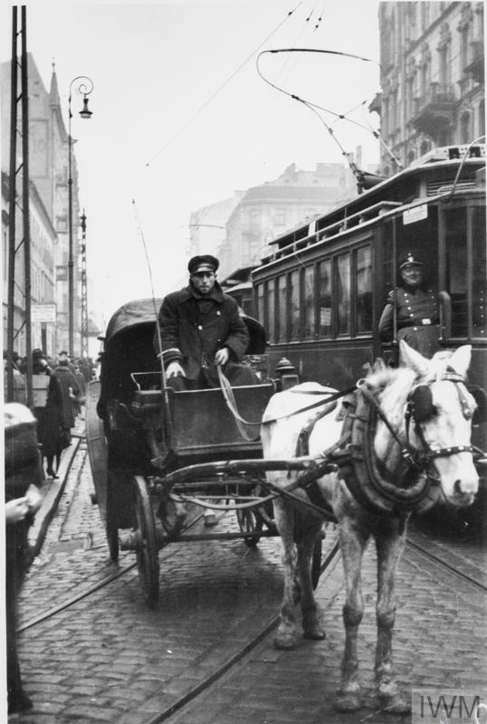 A horse-drawn cab driving alongside a tramcar along Leszno Street in the ghetto. This particular tramline was run between the Muranowski Square and the Grzybowska Street. Note a German officer in the tramcar.