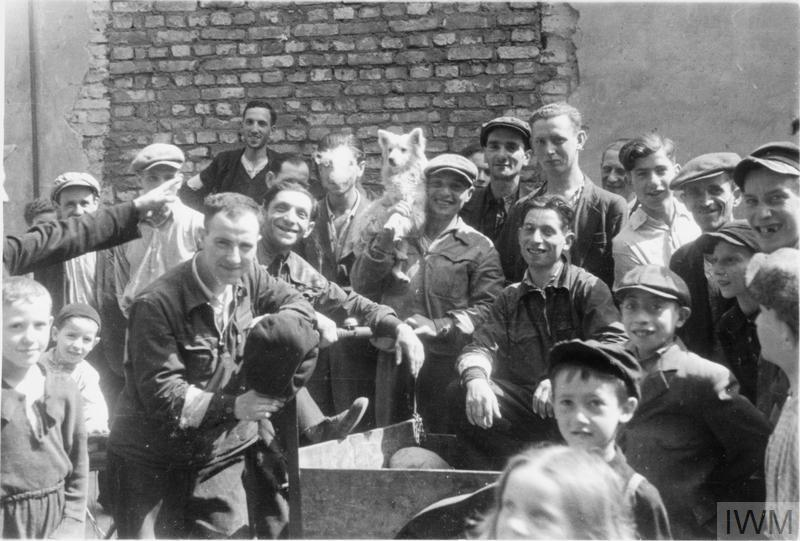 A group of Jewish men and children posing for a photograph in the street of the ghetto. Note the man in the middle, holding a dog on his shoulder.