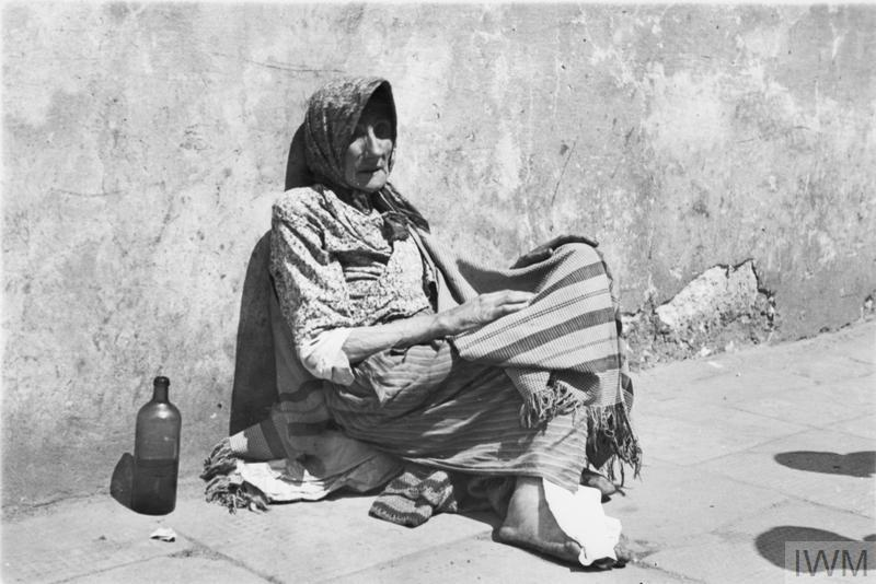 Emaciated elderly woman begging in the street of the ghetto.