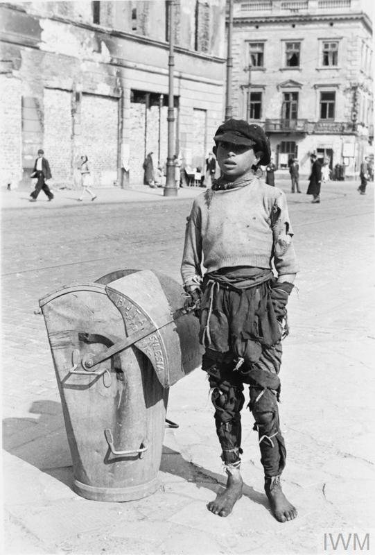 A teenage boy in ragged clothes standing by a waste container (produced by the Silesia Steelworks in Rybnik) in the ghetto.