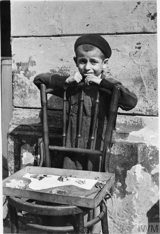 A shy, young boy selling a handful of candies from a chair in the street in the ghetto.