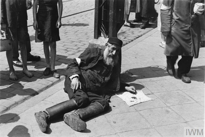 An elderly Jewish man begging on the pavement in the ghetto.