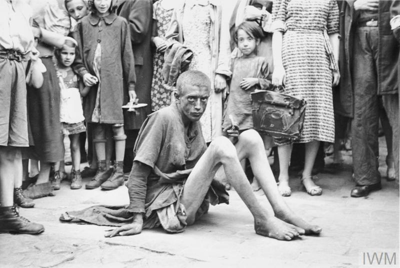 An emaciated Jewish youth seated on a pavement in the ghetto. Note a crowd of pedestrians around him, including children with toys.