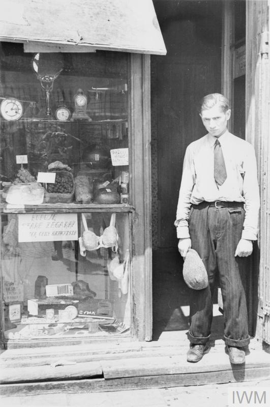 "A young man in the doorway of a shop in the ghetto. Note he has taken his hat off to comply with the German order to remove headwear in the presence of German personnel. The shop offers fresh eggs, sweets and watches. The sign in the window reads - ""I buy old watches for top prices""."