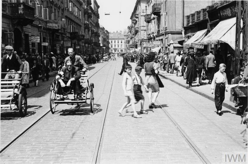 Crowds of pedestrians and street rickshaws in busy Karmelicka Street in the ghetto.
