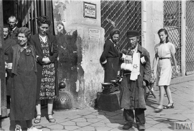A street armband seller and a group of pedestrians on 18 Zamenhofa Street (probably) in the ghetto, summer 1941. Note two advertising plaques on the wall in the background - for Senior Medic (starszy felczer) named J. Singer and for typewriting services (address given - 18 Zamenhofa Street, flat no. 38).