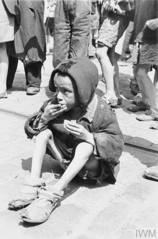 A destitute Jewish child eating a piece of bread in the street of the ghetto, summer 1941.