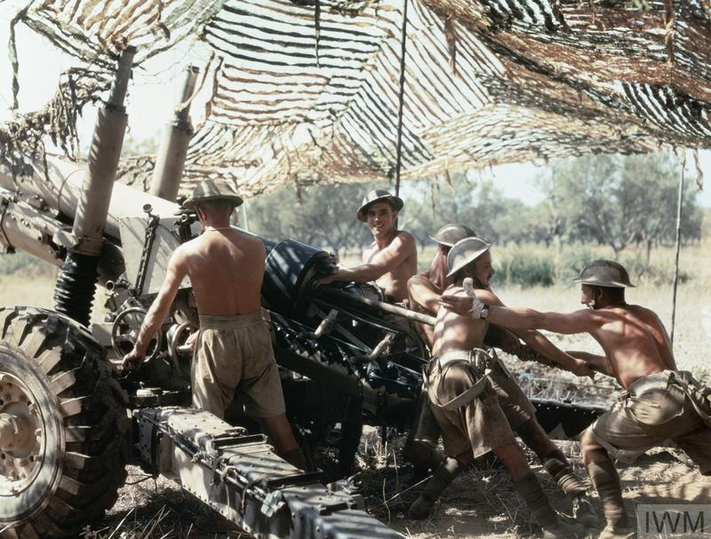 British gunners of the Shropshire Yeomanry in action with a 5.5 inch Howitzer under camouflage netting.