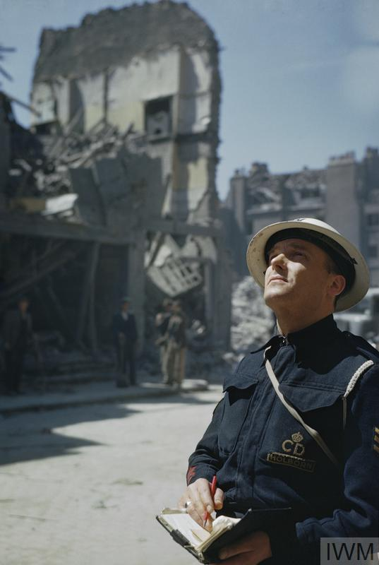 A Civil Defence Warden inspects bomb damaged buildings in Holborn, London.