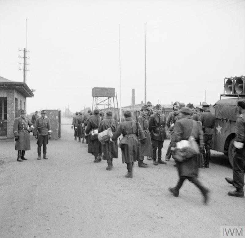 The British Army arrives at Belsen concentration camp. German and Hungarian guards stand at the camp entrance as German Wehrmacht troops (wearing white armbands) enter the camp under the truce agreement reached with the British on 12 April 1945. On the right is a vehicle equipped with loudspeakers from 14 Amplifier Unit, Intelligence Corps under the command of Lt Derrick Sington.