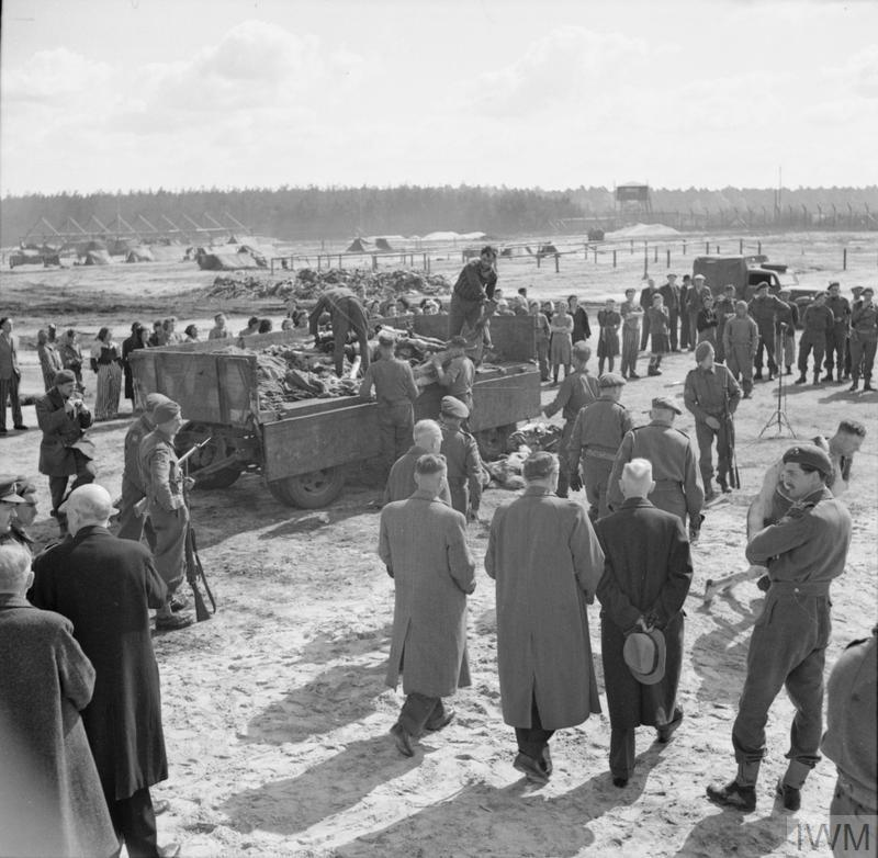 Camp inmates watch German SS guards load a lorry with bodies of the dead. In the foreground, British Army officers escort a party of civilian visitors to the camp.