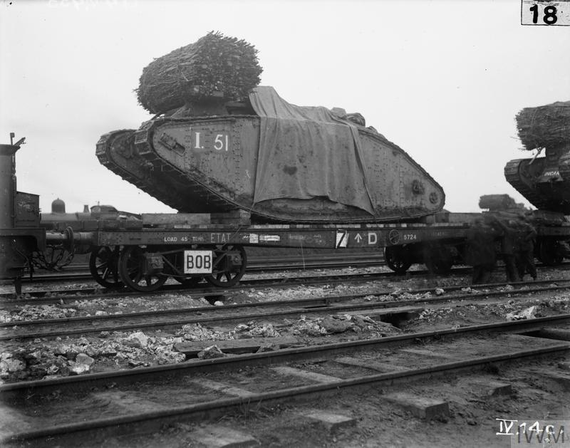 British Mark IV Female Tanks being loaded aboard flat-bed railway trucks at Plateau Station in preparation for transportation to the forward area prior to the opening of the Battle of Cambrai.