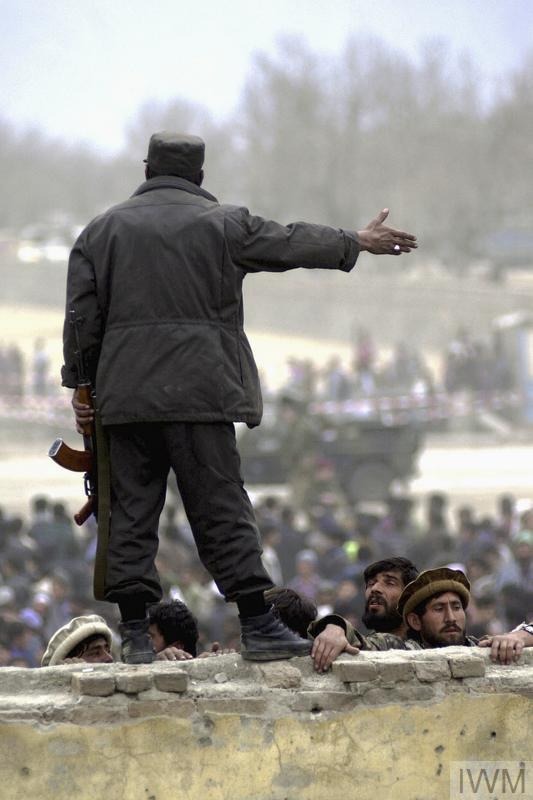 A football match between a local team, Kabul United and ISAF is watched by 30,000 spectators at the Olympic Stadium in Kabul, 15 February 2002. The match was the first international sporting event to take place in Afghanistan in five years. The Taliban regime had used the stadium for public executions. Spectators pour into the stadium, watching from every possible vantage point. An Afghan policeman tries to prevent those without a ticket from scrambling over the wall.