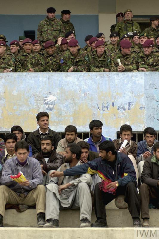 A football match between a local team, Kabul United and ISAF is watched by 30,000 spectators at the Olympic Stadium in Kabul, 15 February 2002. The match was the first international sporting event to take place in Afghanistan in five years. The Taliban regime had used the stadium for public executions. British soldiers for 2 Parachute Regiment and local Afghan supporters watch the match.